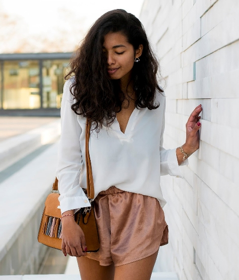 With white loose shirt and yellow tassel bag