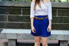 With white off-the-shoulder shirt, blue pleated skirt and white sneakers