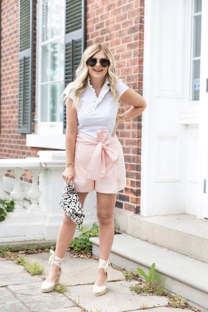With white shirt, printed clutch, pale pink shorts and ankle strap shoes