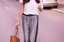 With white t-shirt, flat sandals and brown tote bag