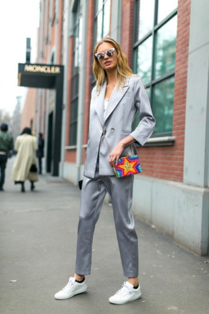 With white top, silver pants, white sneakers and colorful mini bag