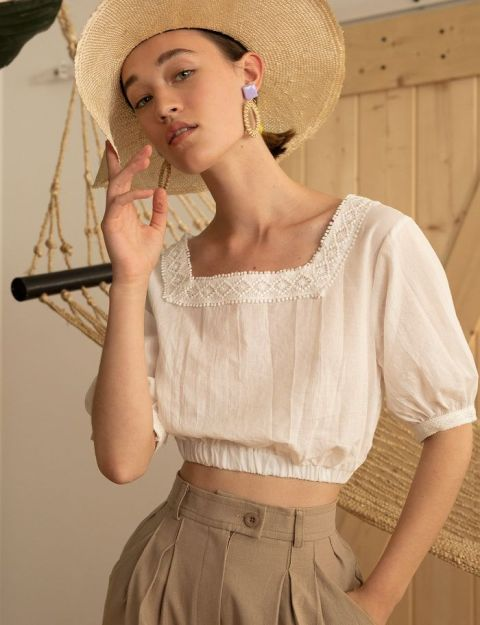With wide brim hat and beige high-waisted loose trousers
