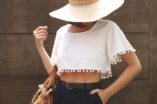 With wide brim hat, brown leather bag and black high-waisted shorts