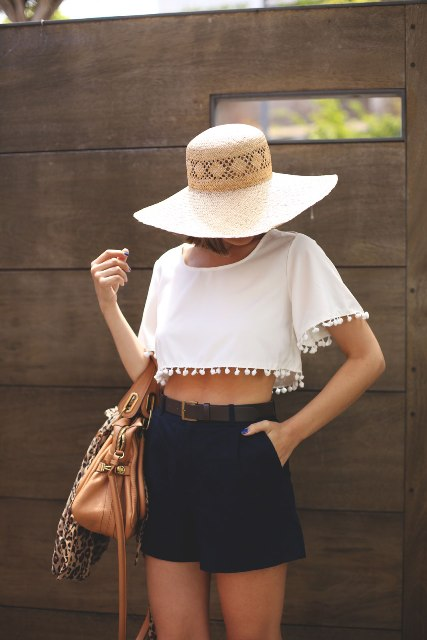 With wide brim hat, brown leather bag and black high waisted shorts