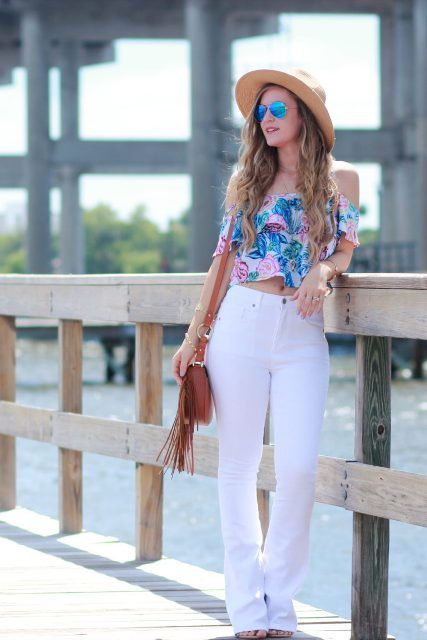 With wide brim hat, white jeans and brown fringe bag