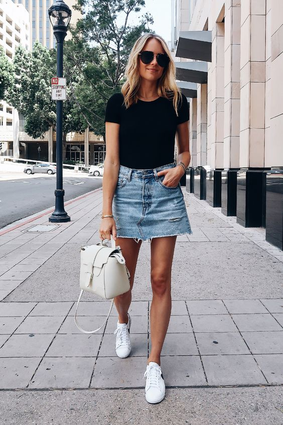 a black tee, a light blue denim mini, white sneakers and a creamy bag for a relaxed summer look