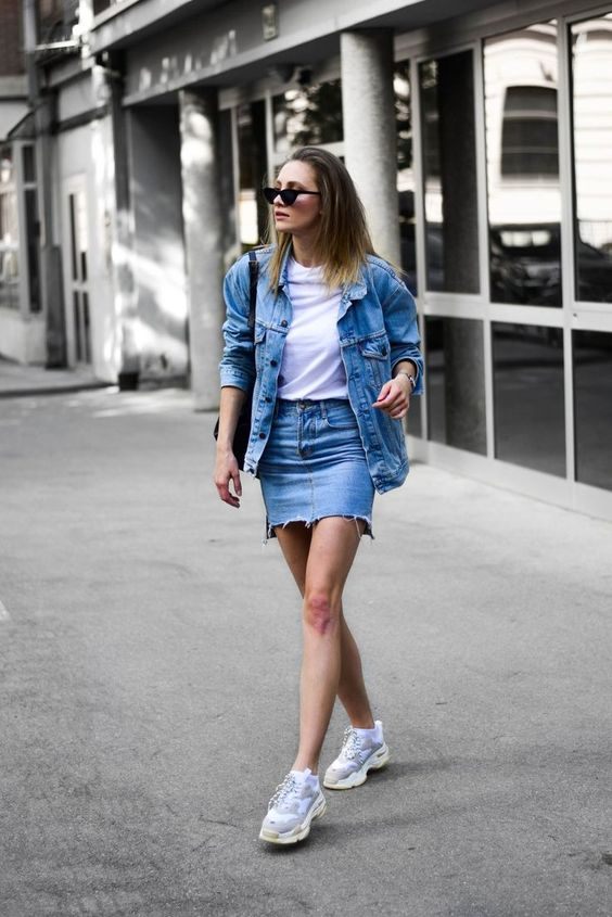 a blue denim mini, a white tee, an oversized blue jacket, neutral trainers and a bag