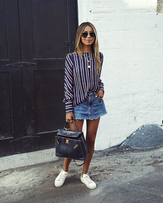 a blue distressed denim mini, a striped blouse, white sneakers and a dark-colored bag