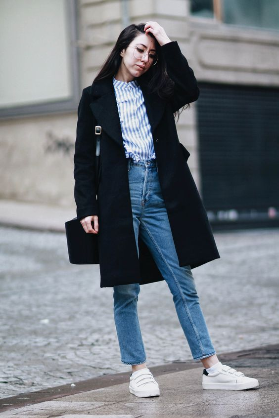 a blue striped shirt, blue mom jeans, white sneakers, a black trench and a black bag