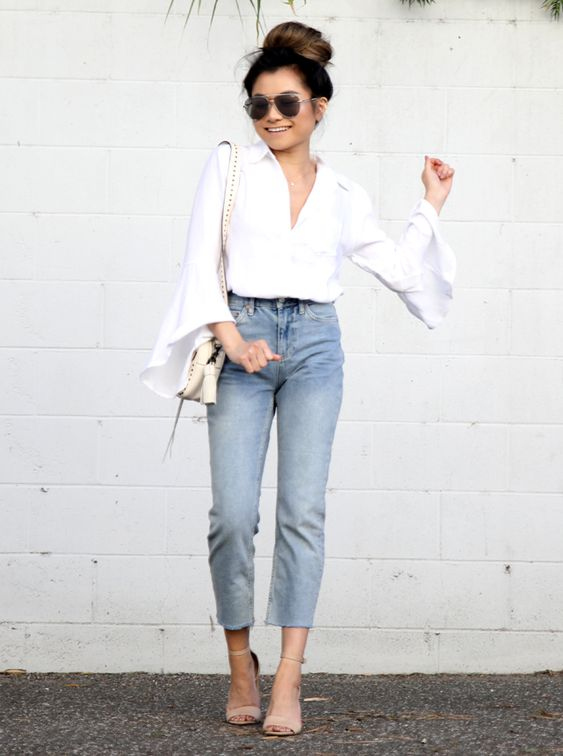 a boho look with a white shirt with bell sleeves and a plunging neckline, blue straight leg jeans, nude heeled sandals and a neutral bag