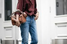 a burgundy silk button down, blue jeans, black strappy shoes and a brown bag