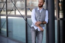 a business casual look with grey jeans, a blue shirt, a grey waistcoat and white sneakers