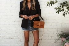 a deconstructed denim mini, a black top, a black blazer, a camel bag and white slipper loafers