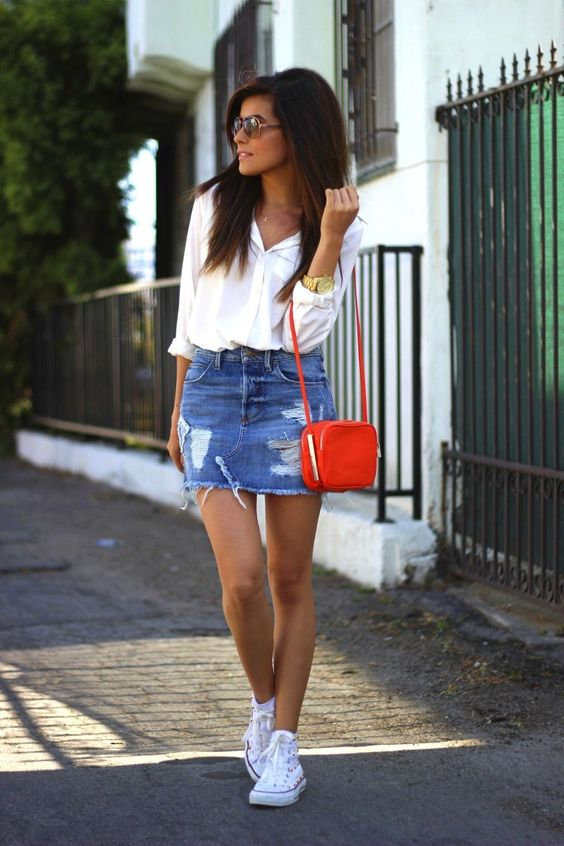 a deconstructed blue denim mini, a white button down, white sneakers and a small red bag for an accent