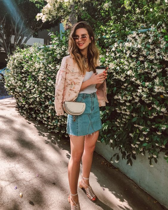 a deconstructed blue denim skirt, a white top, a pink floral denim jacket, a nude bag and strappy shoes