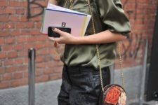 a green silk blouse, black printed pants and a floral round bag on a chain