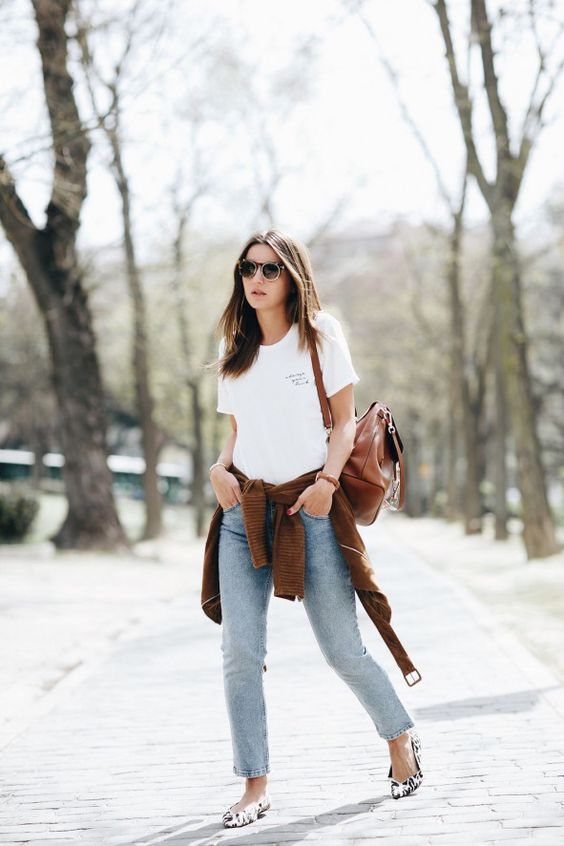 a white printed tee, blue straight leg jeans, a brown cardigan and a brown bag plus leopard flats