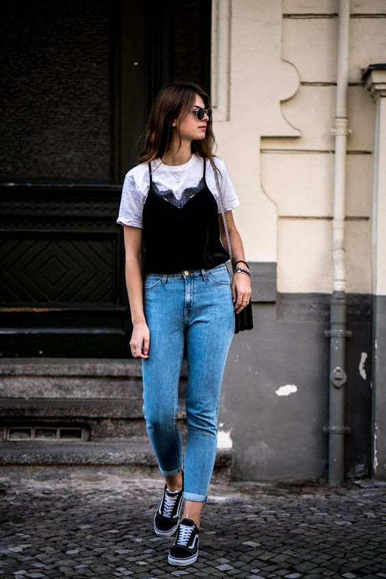 a white tee, a black velvet top, blue mom jeans, black sneakers and a black bag