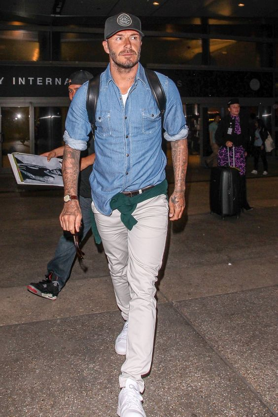 a spring men's look with awhite tee, a chambray shirt, tan pants, white sneakers and a comfy backpack