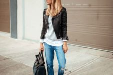 a white tee, a grey jumper, a black leather jacket, blue distressed jeans, printed sneakers and a black bag