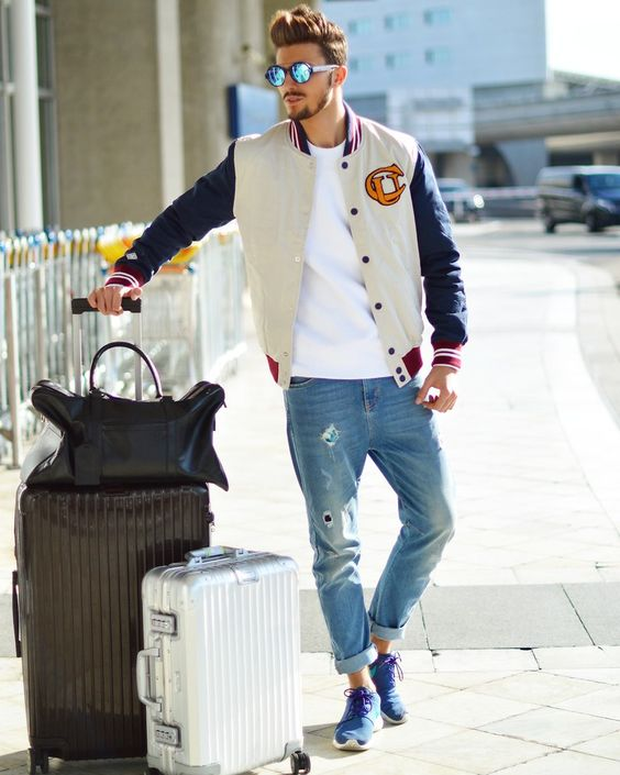a white tee, blue distressed denim, blue trainers and a bomber jacket for a springy look