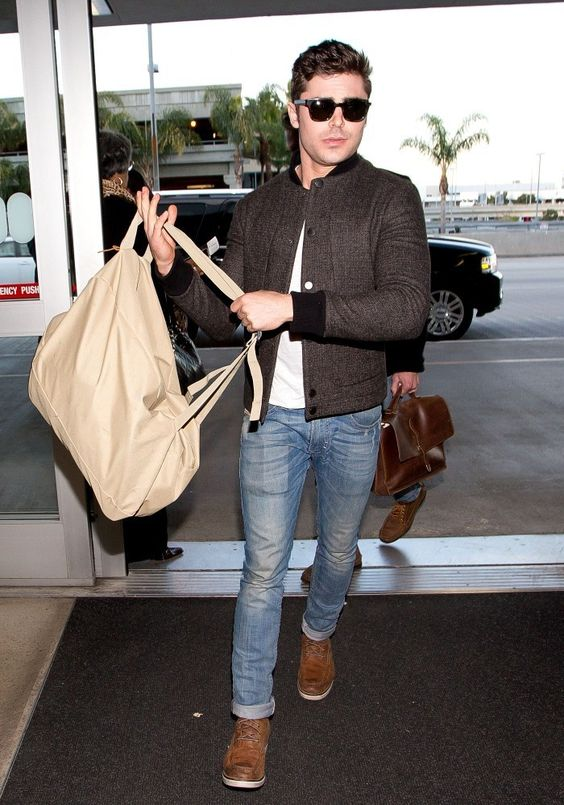 a white tee, blue jeans, brown boots and a brown checked bomber jacket plus a tan backpack