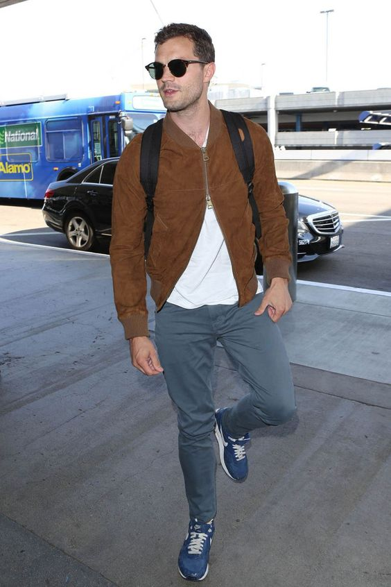 a white tee, grey pants, blue trainers and a brown bomber jacket plus a backpack