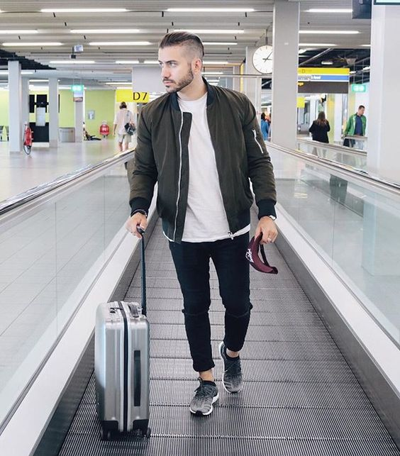 black skinny jeans, a white tee, a black bomber jacket, ombre trainers and a white suitcase