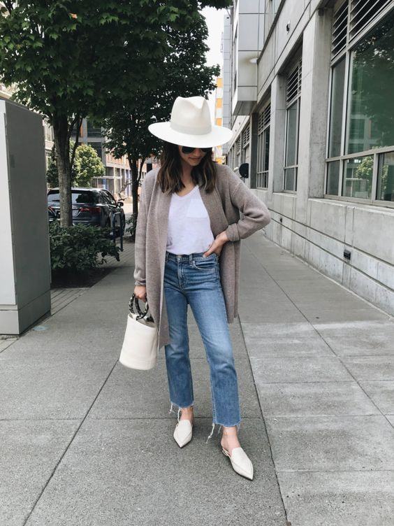 blue straight leg jeans, a white top, a grey cardigan, white slip mules, a white hat and a bucket bag