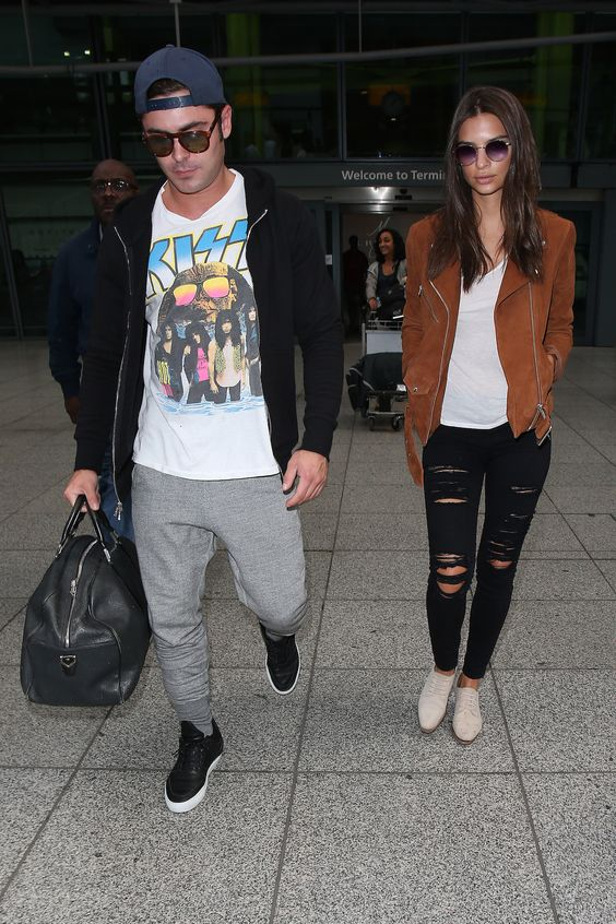 grey sport pants, a printed tee, black trainers, a black bomber jacket and a black bag