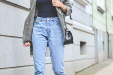 light blue mom jeans, a navy turtleneck, black loafers, an oversized grey blazer, a black cap and a black bag