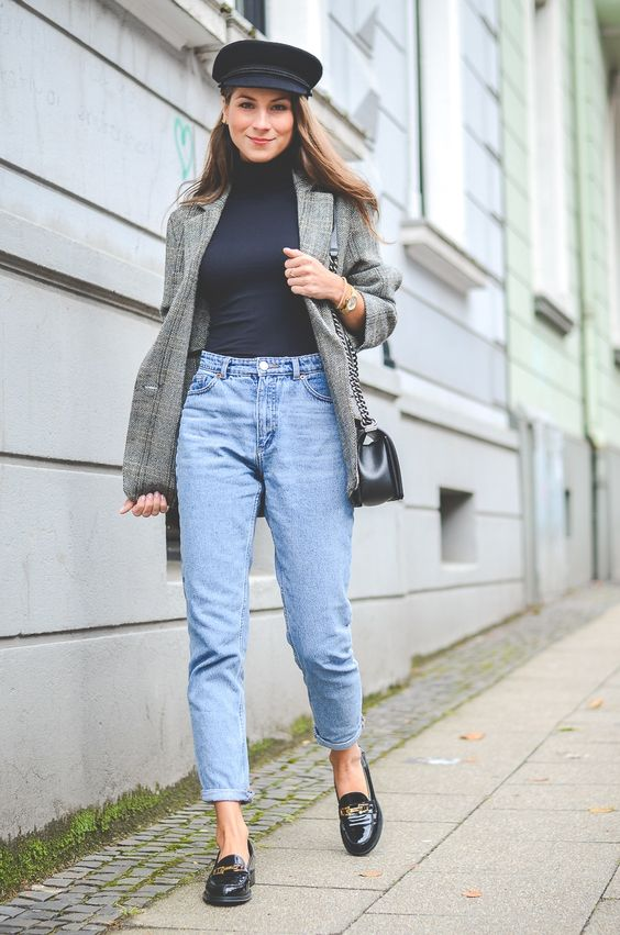 light blue mom jeans, a navy turtleneck, black loafers, an oversized grey blazer, a black cap and a black bag