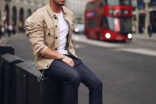 navy jeans, a white tee, white sneakers, a tan denim jacket with black buttons for a casual look