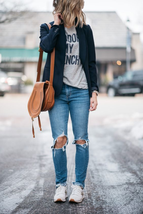 ripped blue mom jeans, a printed grey tee, a black blazer, trainers and a brown bag