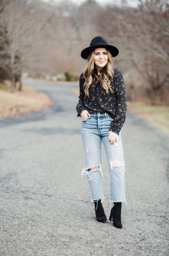 ripped straight leg jeans, black sock booties, a moody floral shirt, a black hat for a boho feel
