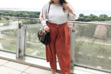 rust-colored culottes, a polka dot blouse, black shoes and a brown bag
