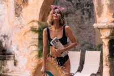 02 a black retro-inspired swimsuit paired with a frigne brim straw hat is a cool outfit for your vacation