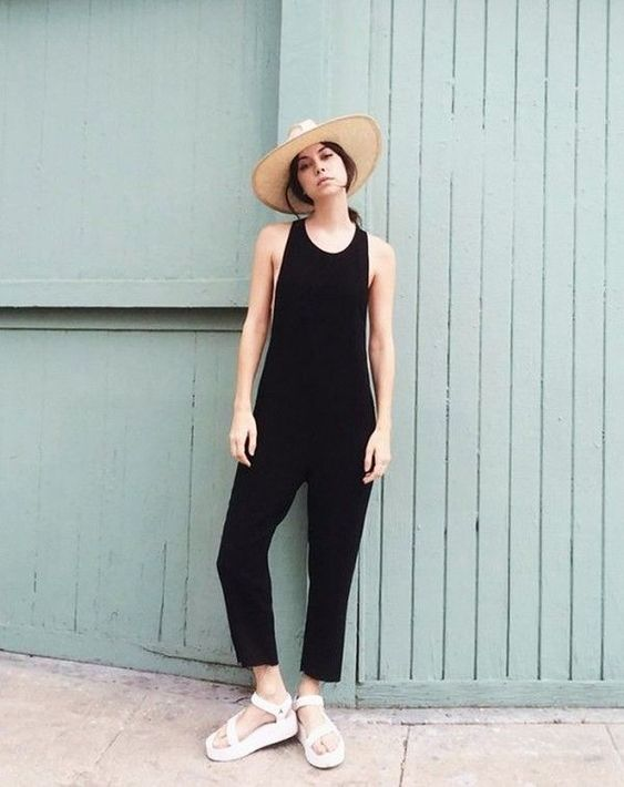 a black sleeveless jumpsuit, white dad sandals and a straw hat for a trendy summer look