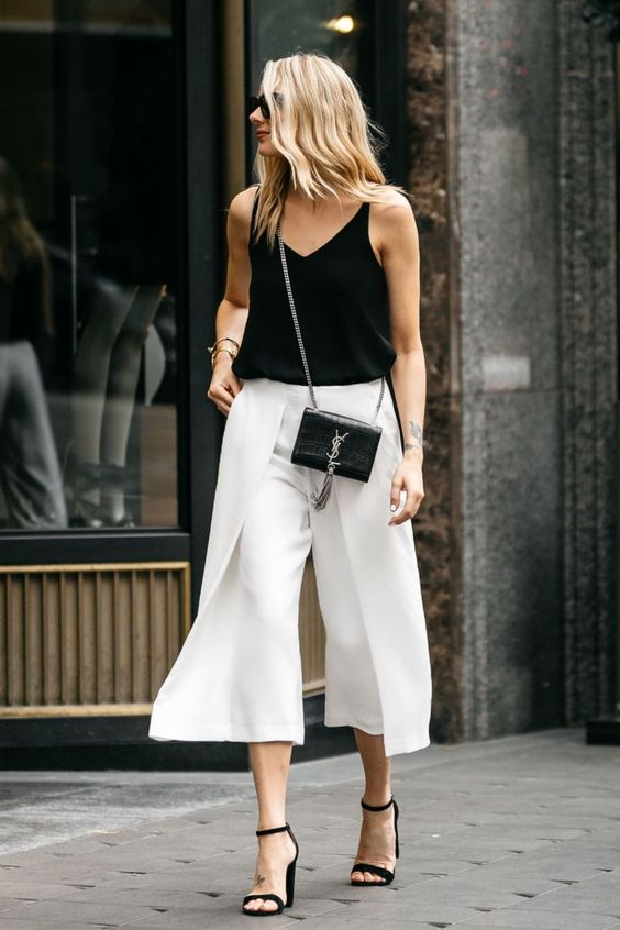 a black strap top, white culottes, black heeled sandals and a black bag for a hot summer work day
