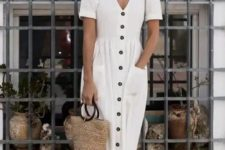 02 a loose white linen midi dress with a row of buttons, strappy sandals, a straw bag