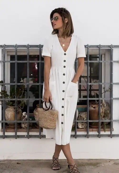 a loose white linen midi dress with a row of buttons, strappy sandals, a straw bag