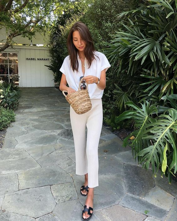 a white oversized button down with short sleeves, pleated cropped pants, black slippers and a straw bag