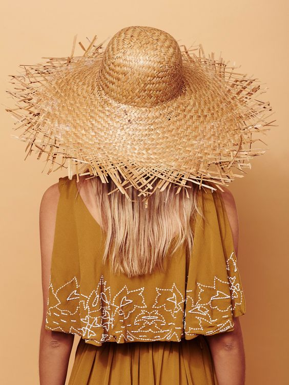 a boho mustard dress with printing paired with a fringe brim straw hat is a cool combo