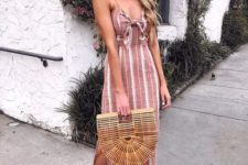 a dusty pink and white striped fitting midi dress, nude heels and a wooden bag