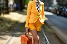 03 a yellow short suit, a white button down, a striped tie, black shoes and an orange bag