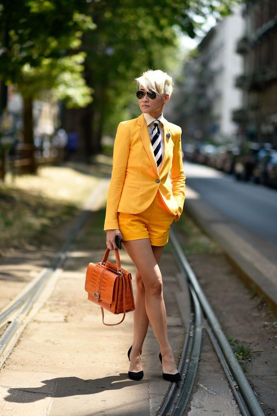 a yellow short suit, a white button down, a striped tie, black shoes and an orange bag