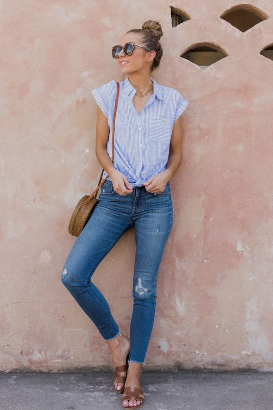 blue skinnies with a ripped hem, a bleu thin stripe cap sleeve button down, brown slippers and a round brown bag