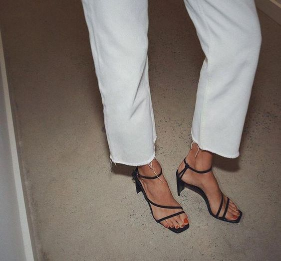 white jeans with a raw hem paired with black heeld sandals with square toes