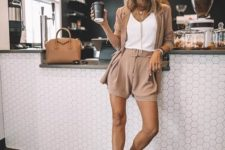 04 a stylish tan shorts suit with a white top, layered necklaces, tan shoes and a camel bag