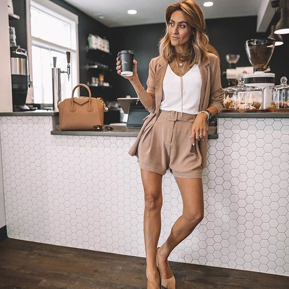 a stylish tan shorts suit with a white top, layered necklaces, tan shoes and a camel bag